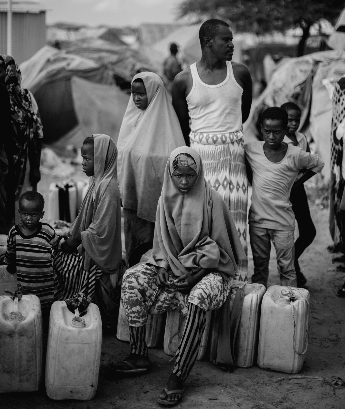 Ludzie czekający w kolejce do ujścia wody w jednym z obozów położonych na obrzeżach stolicy Somalii. Fragment materiału realizowanego dla PAH. Somalia 2018. RAST agencja fotograficzna (fot. Filip Skrońca)