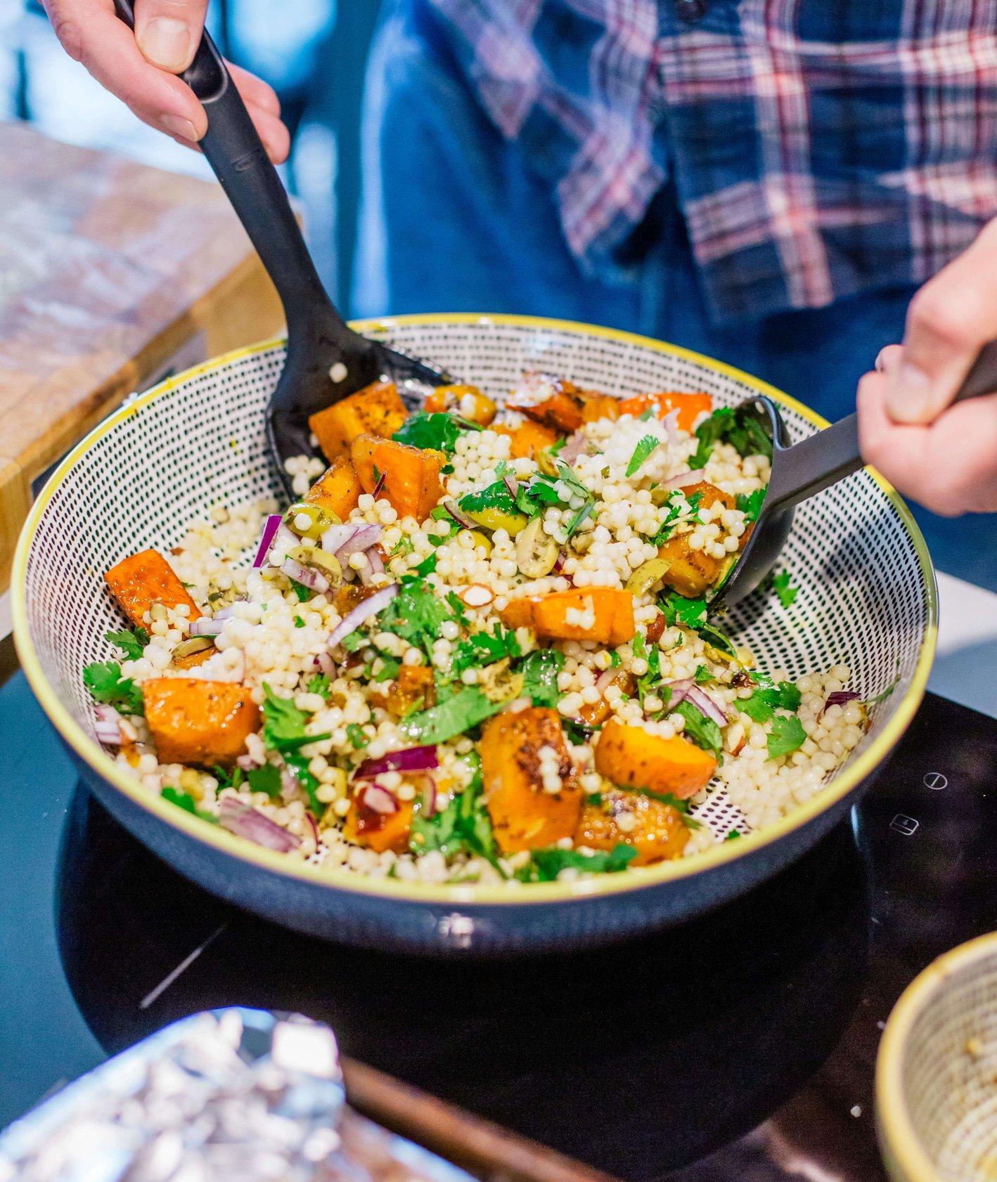 Właściciel restauracji Tomek, miesza w ceramicznej misie składniki sałatki z kaszy bulgur z dynią, czerwoną cebulą, zielonymi oliwkami i kolendrą  (fot. Michał Lichtański)