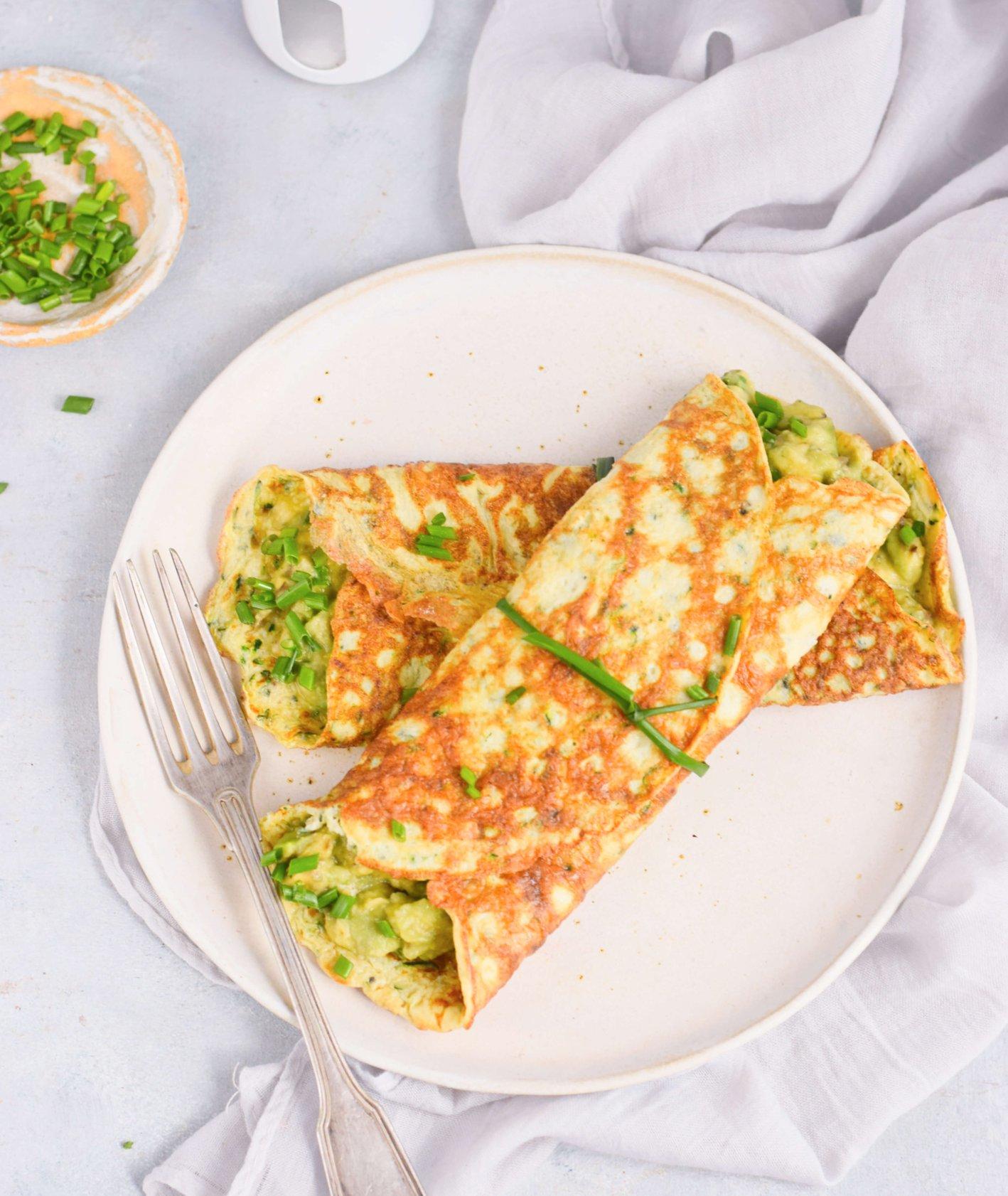 Talerz z omletami cukiniowymi z pastą z awokado, posiekany szczypiorek, solniczka, sztućce i ściereczka (fot. Anna Szewczyk)