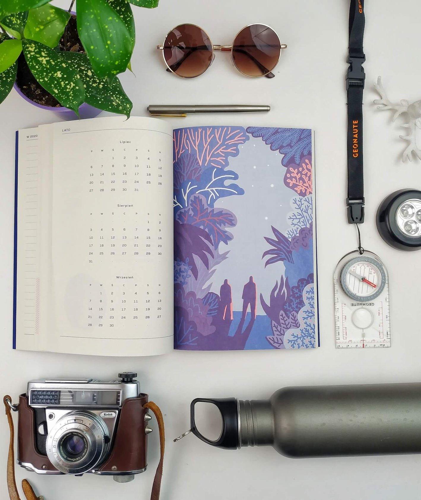 """Rozłożony na stole kalendarz krajoznawczy """"Na dwór"""" z ilustracją przedstawiającą parę wędrująca w zimową noc, obok kalendarza leży kompas, bidon, okulary przeciwsłoneczne, aparat fotograficzny"""